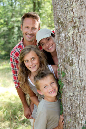 trek: Smiling family standing behind a tree Stock Photo