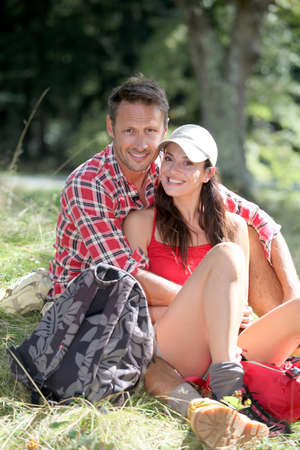 40 years old man: Cheerful couple sitting in forest