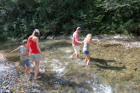 Family crossing a river  photo