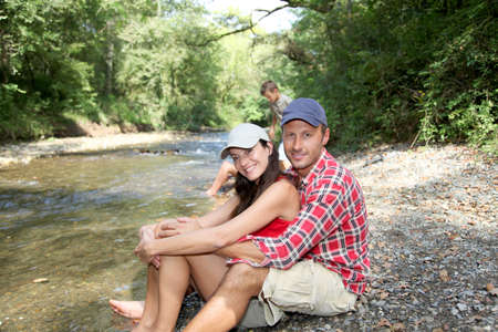 Couple sitting by river in summer photo