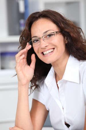 saleswomen: Closeup of smiling businesswoman wearing eyeglasses