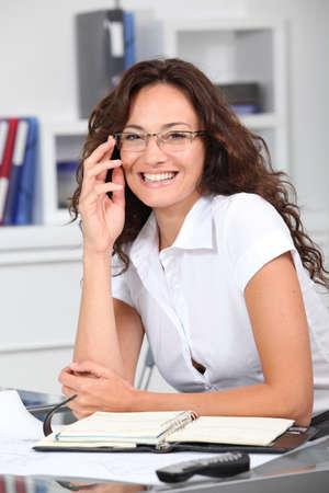 Closeup of smiling businesswoman wearing eyeglasses photo