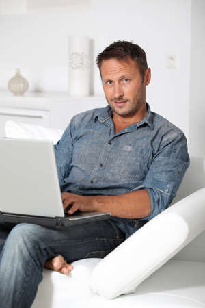 40 years old: Man with laptop computer sitting in sofa Stock Photo