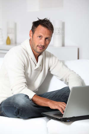 Man with laptop computer sitting in sofa photo