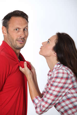 woman 40 years: Angry woman pulling boyfriend shirt neck Stock Photo