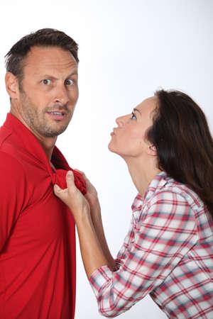 novios enojados: Mujer enfadada tirando a novio cuello de la camisa