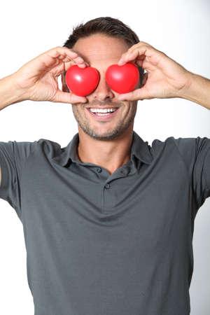 heartbreaker: Hombre que cubre sus ojos con 2 hearts  Foto de archivo
