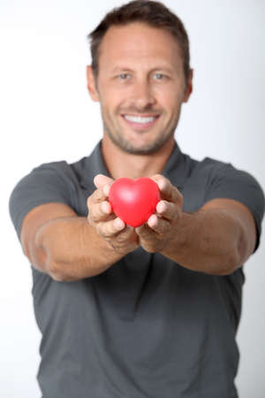 cupid man: Man holding red heart in his hands