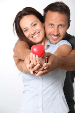 cupids: Couple on white background holding red hearts