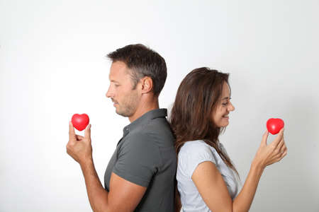 Couple on white background holding red hearts photo