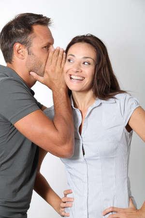 secret love: Man whispering to his girlfriend ear