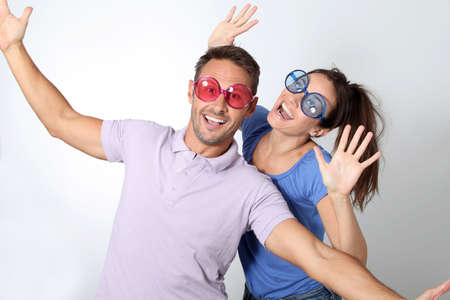 loto: Couple wearing colored glasses having fun on white background Stock Photo