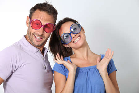 funny faces: Couple wearing colored glasses having fun on white background Stock Photo