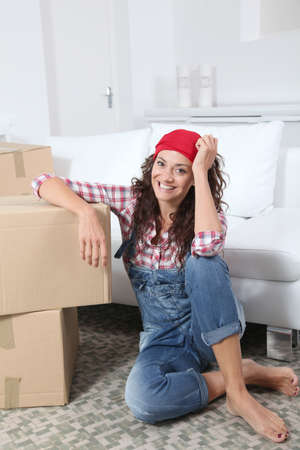 Woman sitting on the floor of living room next to boxes Stock Photo - 7954624