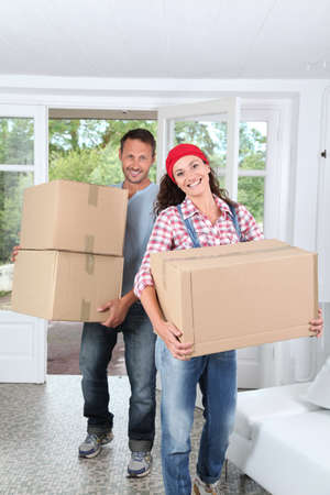 house moving: Couple holding boxes in their new home Stock Photo