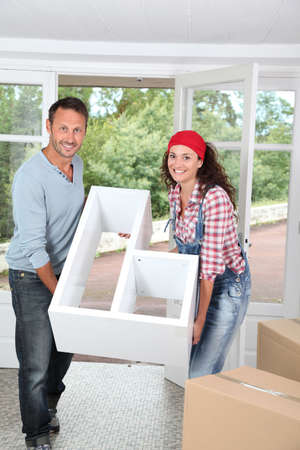 Couple holding furniture in their new home photo