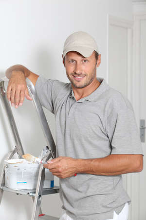 house painter: Man painting walls in white