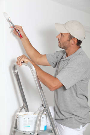 man painting: Man painting walls in white