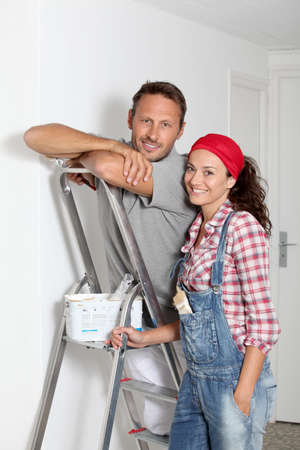 Couple painting walls of their new home photo