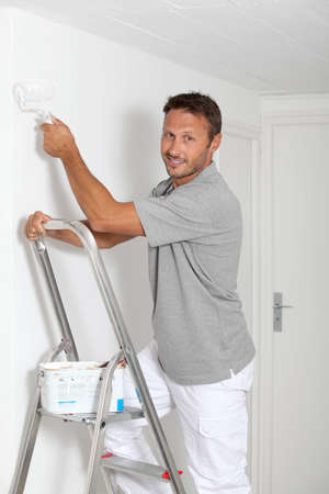 adult wall: Man painting walls in white