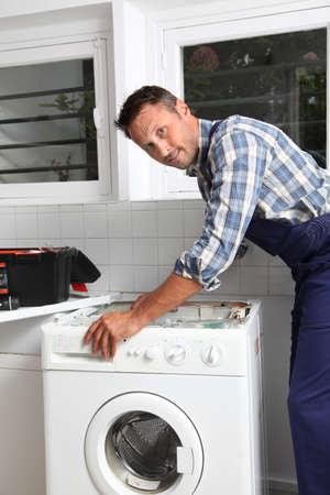 Plumber fixing broken washing machine photo