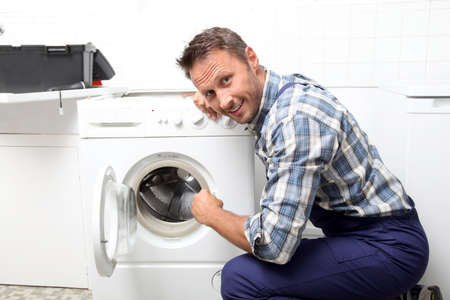 Plumber fixing broken washing machine Stock Photo - 7954264