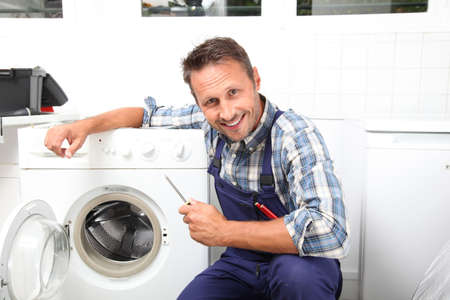 Plumber fixing broken washing machine photo