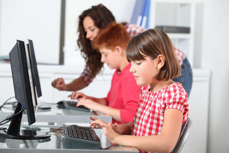 use computer: Teacher and children learning to use computer