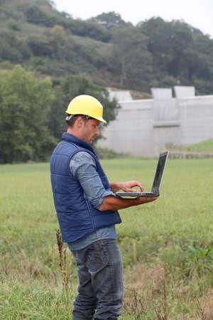 dam: Engineer standing in front of dam under construction