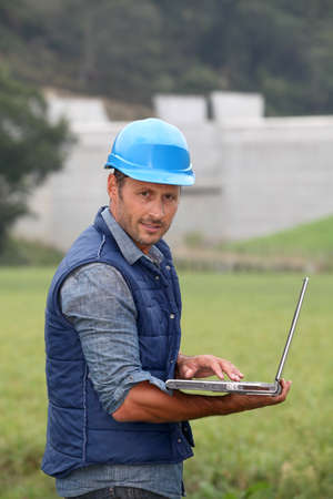 Engineer standing in front of dam under construction photo