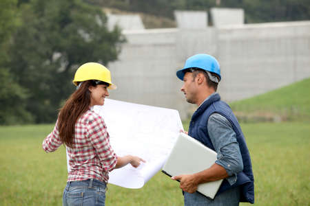Business people checking plan on construction site photo