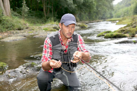 Fisherman in river with fly fishing rod photo