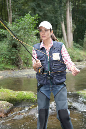 fisherwoman: woman with fly fishing rod in river