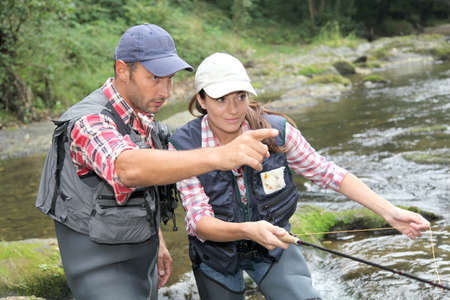 sports fishing: Man and woman fly fishing in river Stock Photo