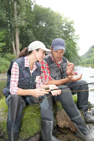 Man and woman fly fishing in river photo