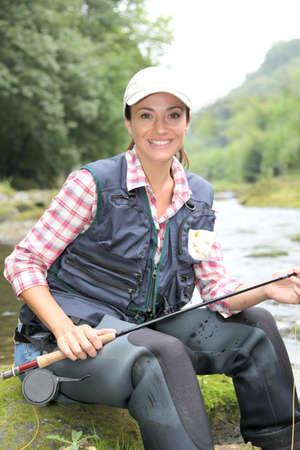 fisherwoman: Fisherwoman sitting on stones in river with fishing rod