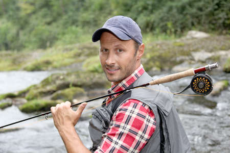 Closeup of fly-fisherman holding fishing rod in river photo