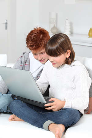 Young boy and girl at home with laptop photo