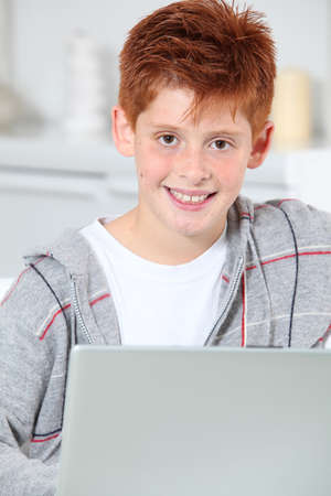 Closeup of young boy at home with laptop computer photo