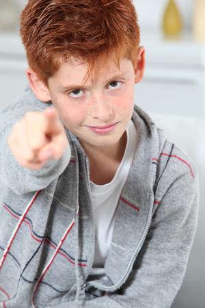 Young boy pointing at camera photo