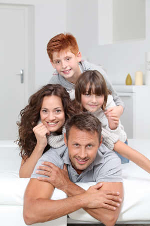 Happy family of 4 people laying on a sofa at home photo