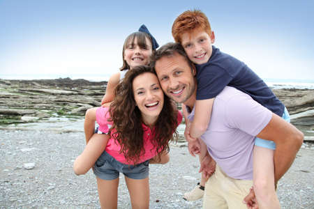 parent and child: Parents doing piggyback to their children Stock Photo