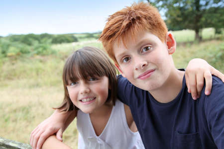 10 years girls: Brother and sister standing in field