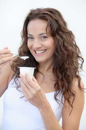 Closeup of beautiful woman eating yogurt Stock Photo - 7954583