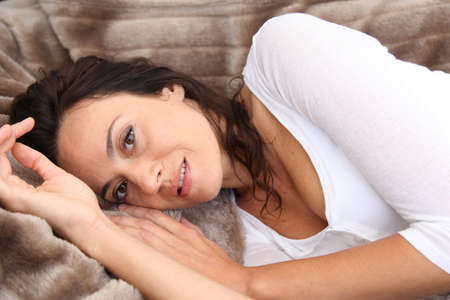 cocooning: Closeup of beautiful woman laying in soft blanket
