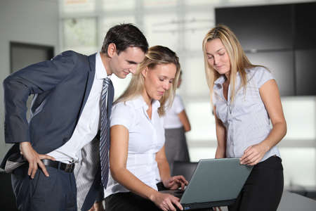 30 years old: Co-workers with laptop computer in the office Stock Photo