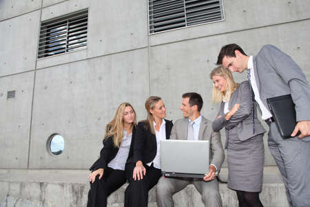 Group of five business people meeting in front of building photo