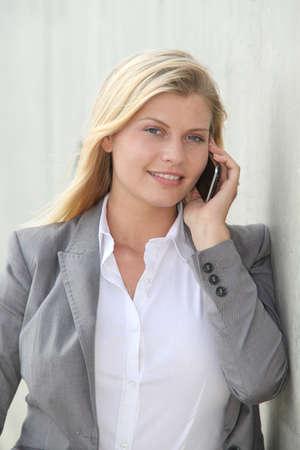 Beautiful blond businesswoman standing outside photo