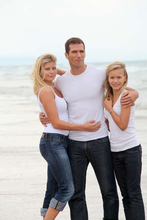 Couple and daughter standing by the sea photo
