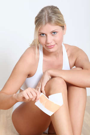 Beautiful blond woman using depilatory wax photo